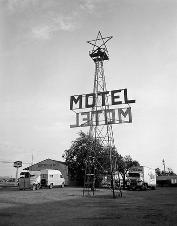 Photograph of a motel advertisement in its environment.