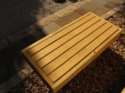 Wooden bench adjacent to walkway