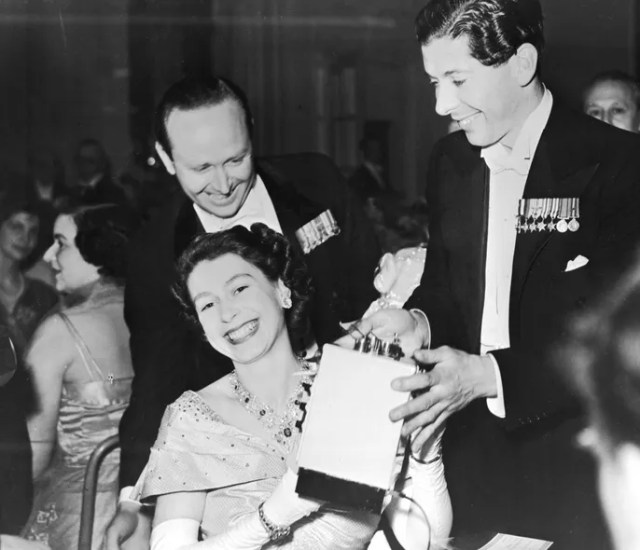 An amused and delighted Princess Elizabeth is presented with a toy cooking stove for Prince Charles by the Honorable Piers St. Aubyn at a flower ball at the Savoy Hotel, London, May 1951.     By George W. Hales/Fox Photos/Getty Images.
