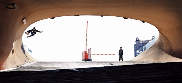 __ORDOS CITY, CHINA__  A security guard looks on at Paul Battlay as he attempts a boneless in a tunnel in Ordos City, a nearly empty ghost town, photographed by Jake Darwen.