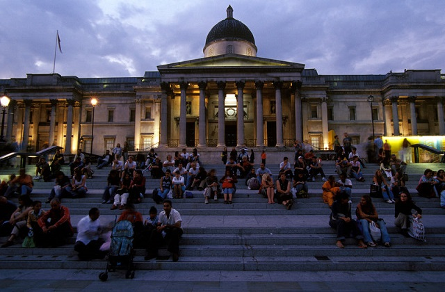 People sitting on steps in front of the National Gallery in Trafalgar Square at dusk.