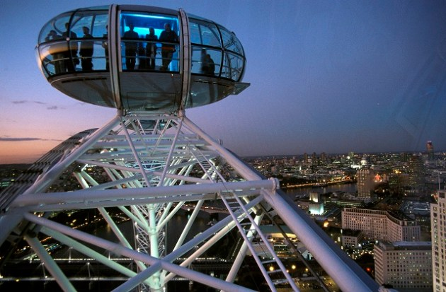 A pod on the London Eye high above the London skyline at night.