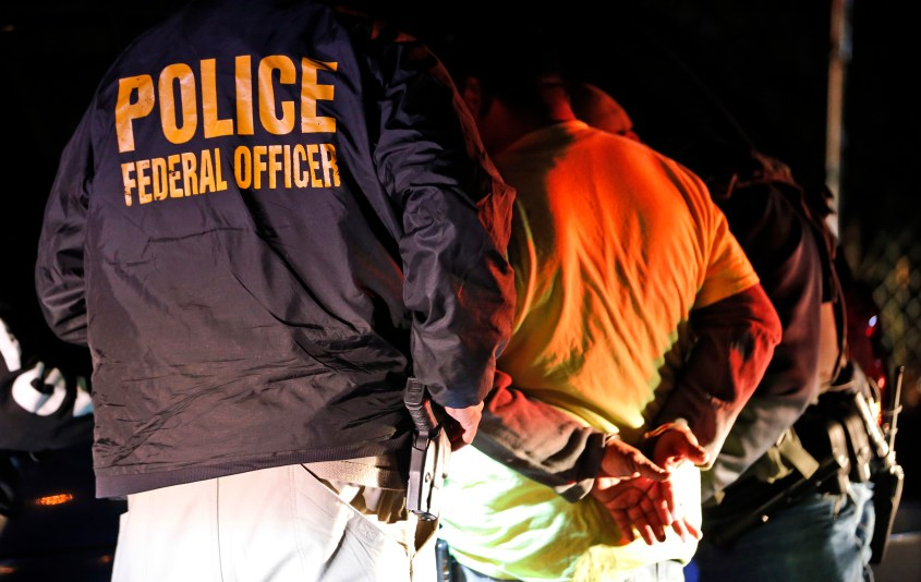 FILE - U.S. Immigration and Customs Enforcement agents surround and detain a person during a raid in Richmond, Va.