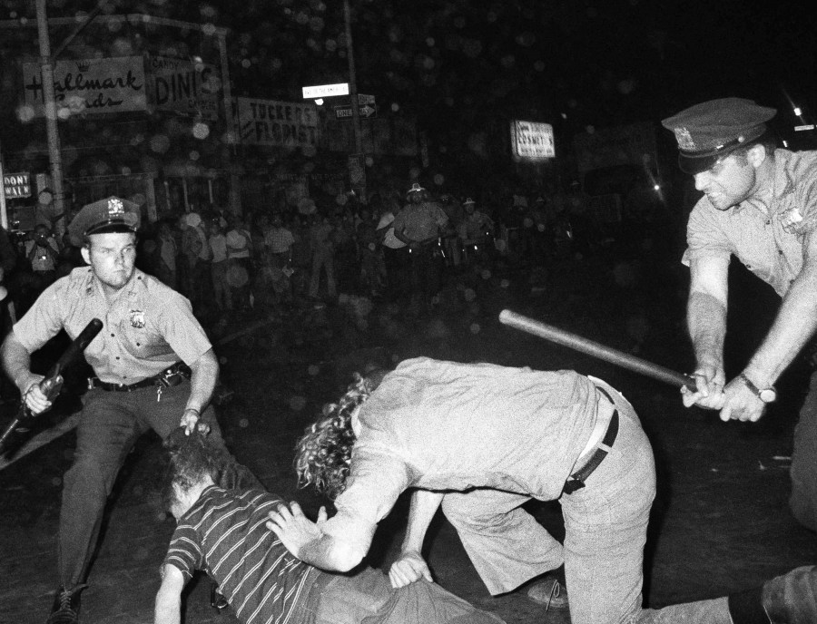 FILE - An NYPD officer grabs a youth by the hair as another officer clubs a young man during a confrontation in Greenwich Village after a Gay Power march in New York,Aug. 31, 1970.