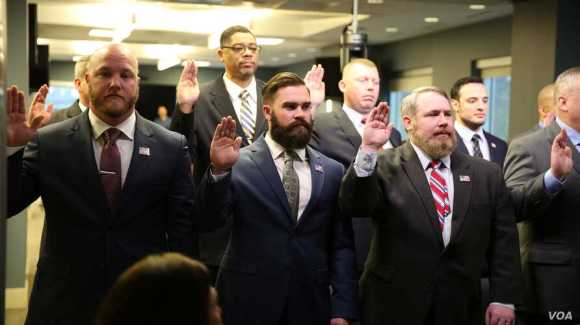 A group of military veterans take the oath at a U.S. Immigration and Customs Enforcement (ICE) ceremony, swearing them in to serve as analysts on child exploitation cases, at ICE headquarters in Washington, March 31, 2017. (B. Hamdard/VOA)
