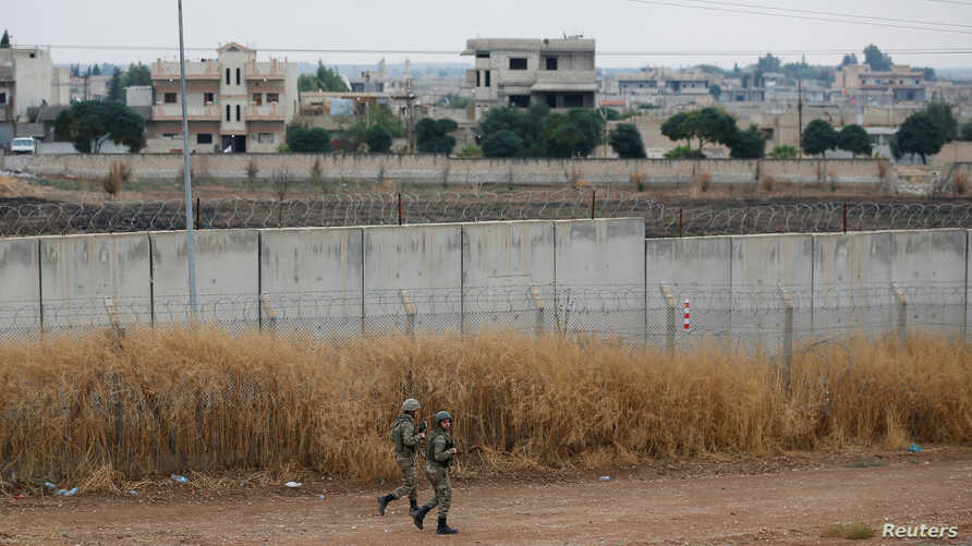 Turkish soldiers patrol along a wall on the border line between Turkey and Syria, in the Turkish border town of Ceylanpinar, in…