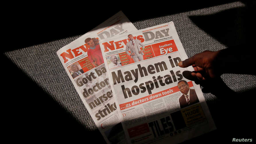 A man picks up a private daily newspaper with a headline on the striking government doctors in Harare, Zimbabwe, September 4, 2019. REUTERS/Philimon Bulawayo