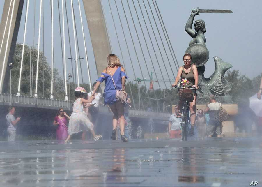 People cool off by the Vistula River during a heatwave in Warsaw, Poland, June 30, 2019.