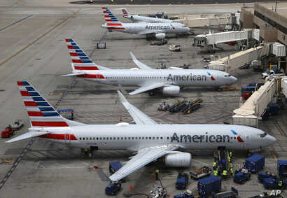 FILE - This July 17, 2019, file photo shows American Airlines planes at Phoenix Sky Harbor International Airport in Phoenix. American Airlines wants two labor unions to pay damages and the companys attorney fees, saying they ignored a judges order