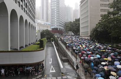 Pro-democracy protestors walk with umbrellas in the rain in Hong Kong, Saturday, Aug. 31, 2019. About 1,000 people were taking part in a Christian march through central Hong Kong on Saturday as a 13th straight weekend of pro-democracy protests got…