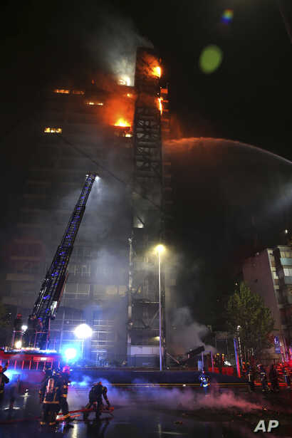 Firefighters work to put out the flames rising from the Enel Energy Europe building set on fire by protesters against the…
