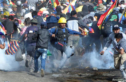 Coca growers, supporters of former President Evo Morales, run away from tear gas as one of them kicks a tears gas canister