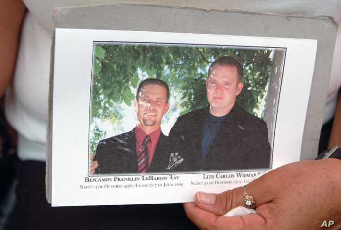 A woman holds a picture of Mormon anti-crime activist Benjamin LeBaron, left, and his neighbor Luis Widmar, who were killed, during funeral services in Galeana, Mexico, July 9, 2009.