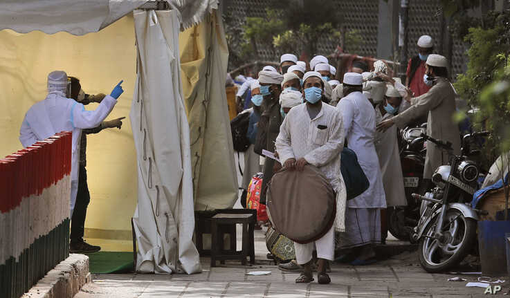 FILE - Indian paramedics, left, screen Muslims to be taken by bus to a coronavirus quarantine facility, in the Nizamuddin area of New Delhi, India, March 31, 2020.