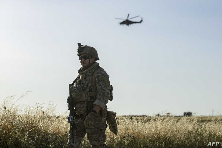 A picture taken on June 3, 2020 shows a US soldier standing guard as a Russian military helicopter flying over the northeastern…