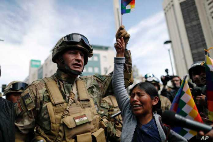A woman cries in front of soldiers guarding a street during a march of supporters of former President Evo Morales in downtown