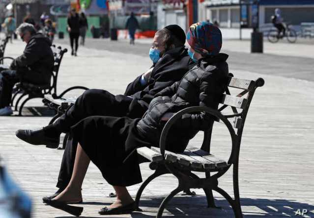 A Jewish man and woman wear face masks as they sit on a bench in the sun Thursday, April 2, 2020, at the Coney Island boardwalk…