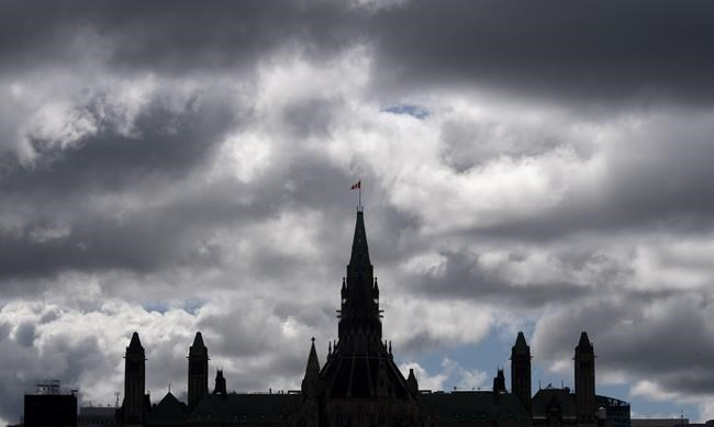 Clouds pass by the parliament buildings Wednesday August 19, 2020 in Ottawa. THE CANADIAN PRESS/Adrian Wyld