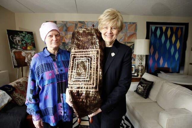 Irma Penn (right) holds bag that will contain the Torah scroll she is working on. With her is Ruth Livingston, past-president of Temple Shalom.