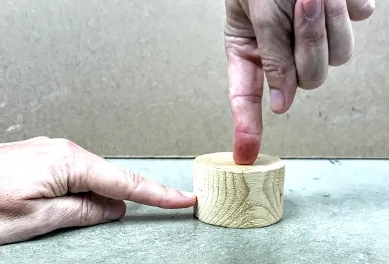 a cylinder with a finger pointing down on it and a finger pointing to it's side