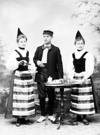 """En påg och två töser i Rättviksdräkt gör reklam för lemonaden """"Smällkork""""."""