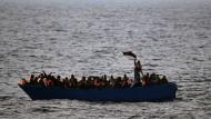 Geflüchtete aus Afrika rufen 2017 auf dem Mittelmeer in einem Boot um Hilfe.