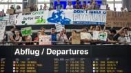 Diese Demonstranten am Stuttgarter Flughafen wollen die Menschen vom Fliegen abhalten.