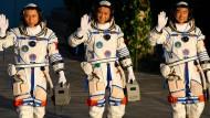 Die chinesischen Astronauten Tang Hongbo (l-r), Nie Haisheng und Liu Boming winken vor dem Start.
