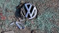 Ein zerbrochenes VW-Logo liegt auf einem Schrottplatz.