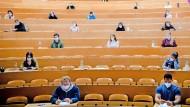 Studierende sitzen am 1. März 2021 in einem Hörsaal kurz vor einer Klausur mit Sicherheitsabstand an der Goethe-Universität in Frankfurt am Main.