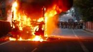 Widerstand gegen das Staatsbürgerschaftsgesetz: Ein Bus brennt auf einer Straße in Neu-Delhi.