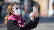 Eine Frau fotografiert mit ihrem Smartphone am Berliner Alexanderplatz.