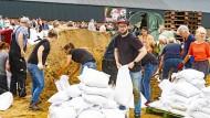 Helfer füllen in der Stadt Venlo Sandsäcke.