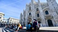 Touristen sitzen mit Schutzmasken auf den Stufen der Kathedrale in Mailand.