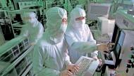 Zwei Arbeiter von TSMC arbeiten im Reinraum einer Chipfabrik.