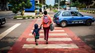 Eine Mutter mit einem Rucksack überquert mit ihrem Sohn einen Zebrastreifen in Bezirk Kiyovu
