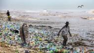 Ein Mann sammelt 2016 verwertbares Material am verschmutzten Korle Gono Strand in Ghana.