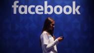 Eine Frau steht mit ihrem Smartphone unter dem Facebook-Schriftzug.
