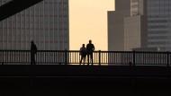Zweisamkeit plus eins: im Abendlicht zwischen den Hochhäusern von Frankfurt
