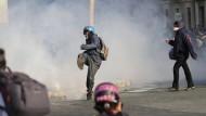 Ein Demonstrant steht im französischen Bayonne bei Protesten gegen den G-7-Gipfel in einer Wolke aus Tränengas