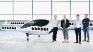 Ein Flugtaxi und die Unternehmensgründer Sebastian Born (von links), Patrick Nathen Daniel Wiegand und Matthias Meiner