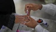 Indien, Muzaffarnagar: Ein Wahlhelfer färbt in einem Wahllokal im Dorf Shahpur den Finger eines Wählers mit Tinte ein.
