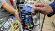 Ein Kunde bezahlt an einer Supermarktkasse kontaktlos mit einer Girocard.
