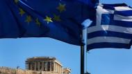 Die europäische und die griechische Fahne wehen vor der Akropolis im Wind.