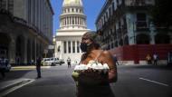 Eine Frau mit einer Packung Eier – im Hintergrund das Kapitol in Havanna
