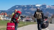 Die Zugausfälle und gesperrten Grenzen wirken sich auch auf Heimkehrer aus: Diese beiden müssen aus dem österreichischen Kufstein ins bayerische Kiefersfelden laufen, um dort in einen deutschen Zug umsteigen und weiterfahren zu können.