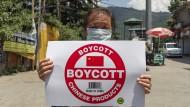 Ein Exil-Tibeter hält ein Schild bei einer Protestakton des Tibetischen Jugendkongresses mit Aufruf zum Boykott chinesischer Waren.