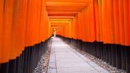 Das Imago der japanischen Frau, hier dezent als ferne Erscheinung im Kimono auf einem Torii-Weg am Shinto-Schrein Fushimi Inari-Taisha in Kyoto