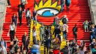 Buntes Treiben im März 2019: Besucher auf dem Treppenaufgang zu den Buchmesseständen in der Glashalle des Leipziger Messegeländes