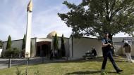 Neuseeland, Christchurch: Ein bewaffneter Polizist patrouilliert auf dem Gelände der Al-Nur-Moschee, die nach dem Terroranschlag wiedereröffnet wurde.